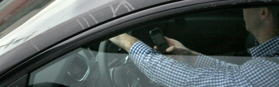 man texting while driving
